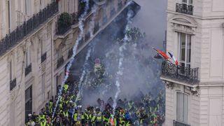 'Yellow vest' protesters clash with riot police amid tear gas on the Champs Elysees in Paris