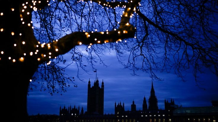 Christmas lights illuminate a tree as nighttime falls over the Houses of Parliament