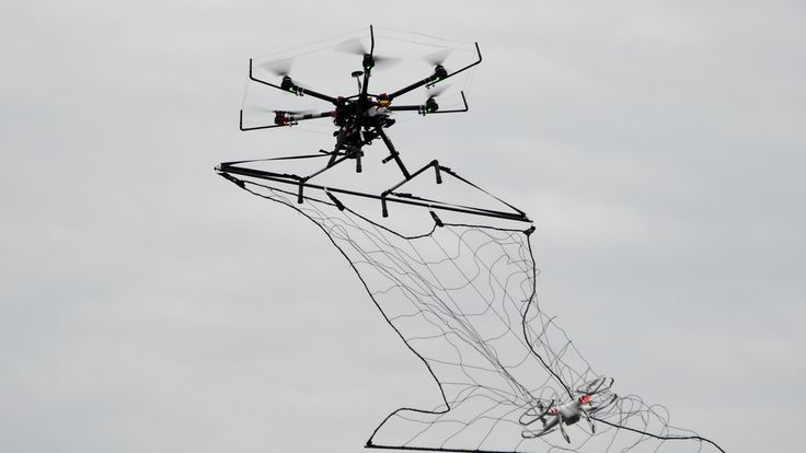 A police drone interceptor (top) snags another drone with a net during an anti-terrorism drill for the upcoming Tokyo marathon at the planned finish area for the event in Tokyo on January 17, 2016. Some 400 people including organizing staff, police and coast guard officers participated in the drill. AFP PHOTO / TOSHIFUMI KITAMURA / AFP / TOSHIFUMI KITAMURA (Photo credit should read TOSHIFUMI KITAMURA/AFP/Getty Images)