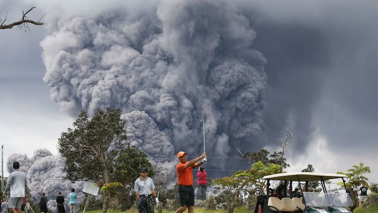 People play golf as an ash plume rises in the distance from the Kilauea volcano on Hawaii's Big Island. The U.S. Geological Survey said a lowering of the lava lake at the volcano's Halemaumau crater 'raised the potential for explosive eruptions' at the volcano