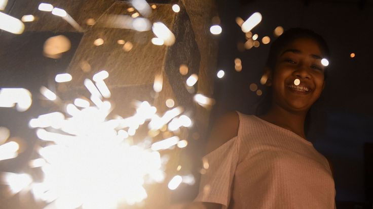 A young woman holds a sparkler during New Year's celebrations in Colombo, Sri Lanka, on January 1, 2019. (Photo by ISHARA S. KODIKARA / AFP) (Photo credit should read ISHARA S. KODIKARA/AFP/Getty Images)