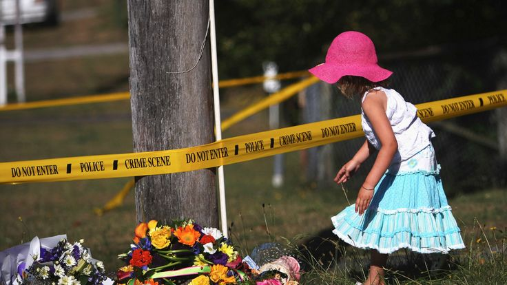 Young girl leaves flowers for murdered Scottish tourist Karen Aim at the site of her death near Taupo's Nui-a-Tia College on January 18, 2007 in Taupo, New Zealand