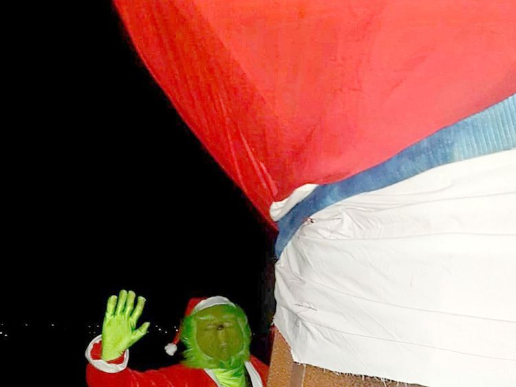 A person dressed as Dr Seuss character the Grinch, removes a Santa hat on the 20 metres tall steel sculpture 'Angel of the North', outside Gateshead, Tyne and Wear