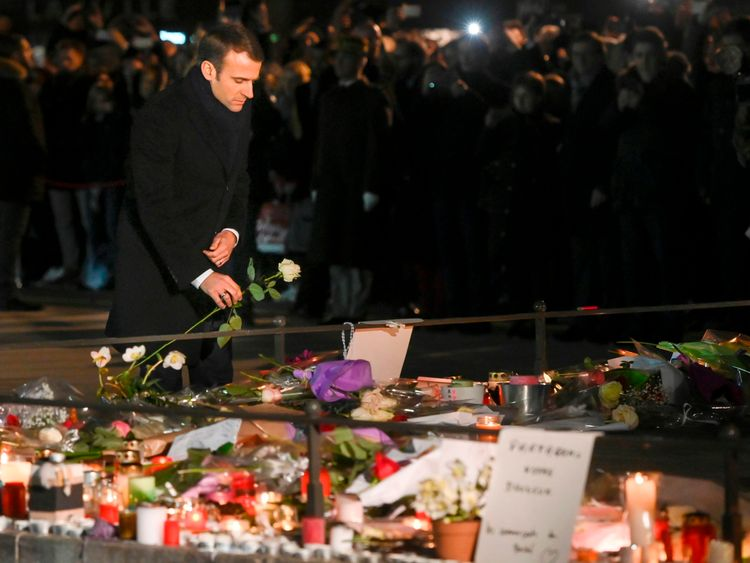 French President Emmanuel Macron lays a white rose at a monument near the Christmas market in Strasbourg, eastern France, used as a makeshift memorial for the victims of the December 11 attack who killed four people
