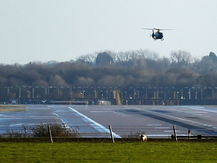 A police helicopter flies over the runway at Gatwick airport which was closed after drones were spotted over the airfield