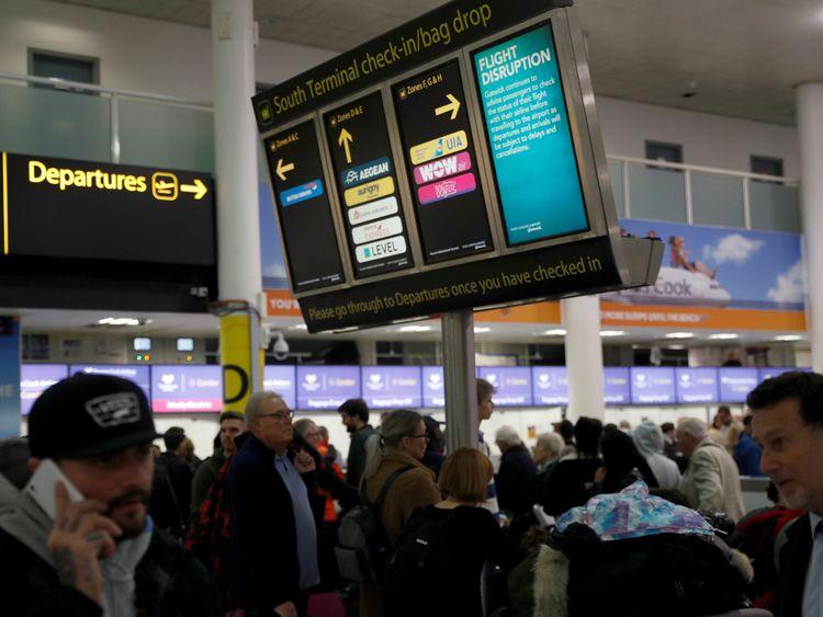 Passengers walk beneath screens displaying travel information in Gatwick Airport, in Crawley, Britain, December 22, 2018