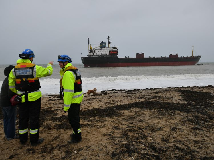 Rescue workers stand on the shore as the refloat operation takes place
