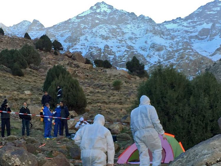 Police officers work next to a tent where the bodies of two Scandinavian women were found