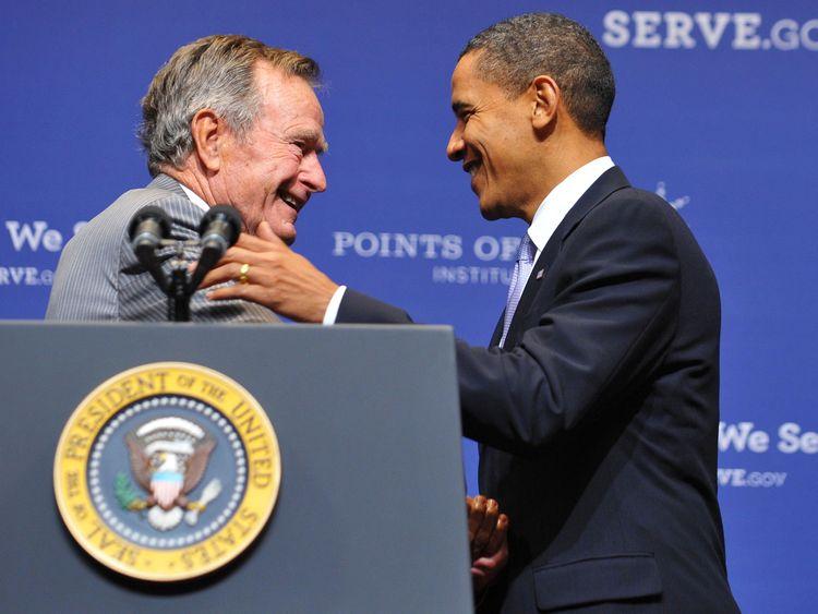 Former US president George H.W. Bush (L) greets President Barack Obama after introducing him on October 16, 2009