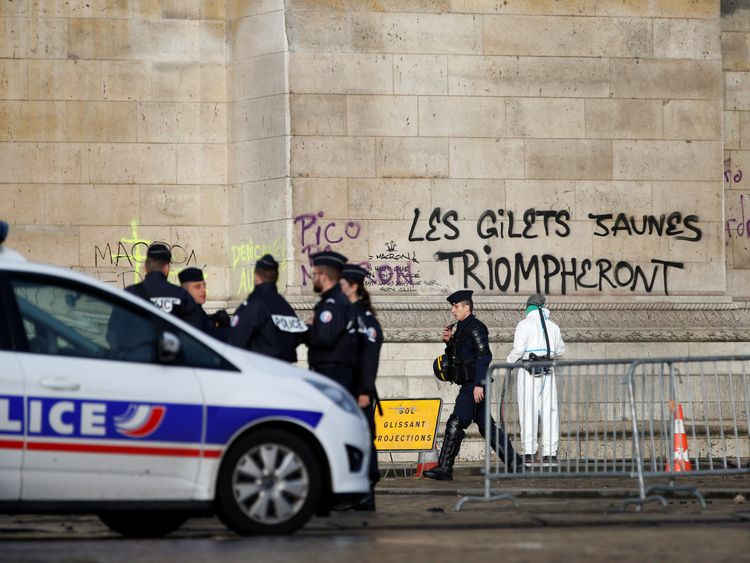 Cleaners scrubbed off graffiti reading 'the yellow vests will triumph' from the Arc de Triomph before Mr Macron's visit