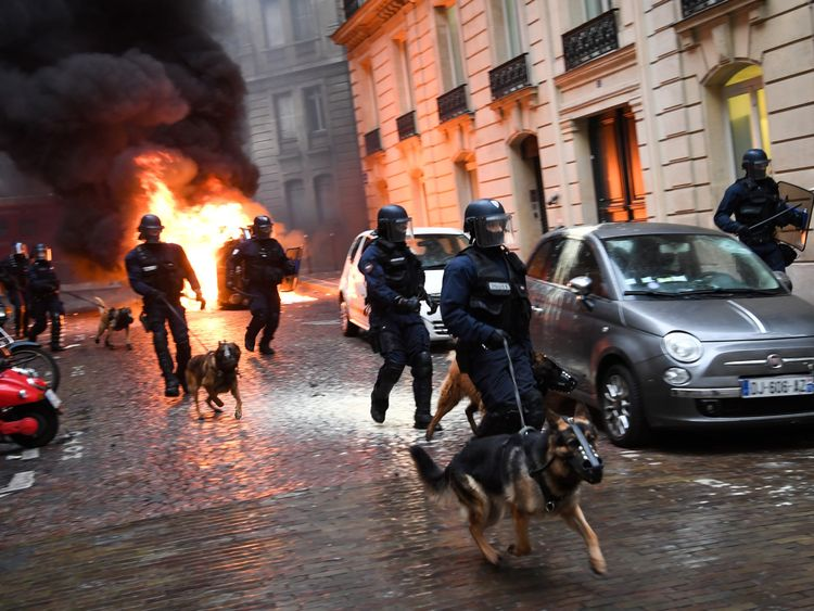 Riot police run next to a car off the Champs-Elysees in central Paris