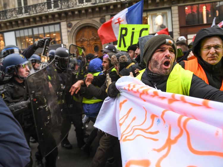 Protesters clash with riot police at Place de l' Opera during the 'yellow vests' demonstration on December 15, 2018 in Paris