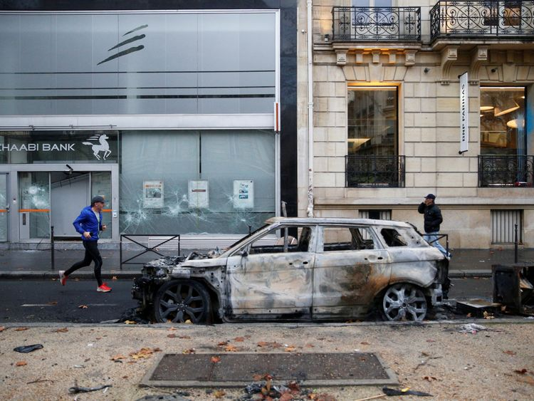 A vandalized car and bank front are seen the morning after clashes with protesters wearing yellow vests, a symbol of a French drivers' protest against higher diesel fuel taxes, in Paris, France, December 2, 2018.