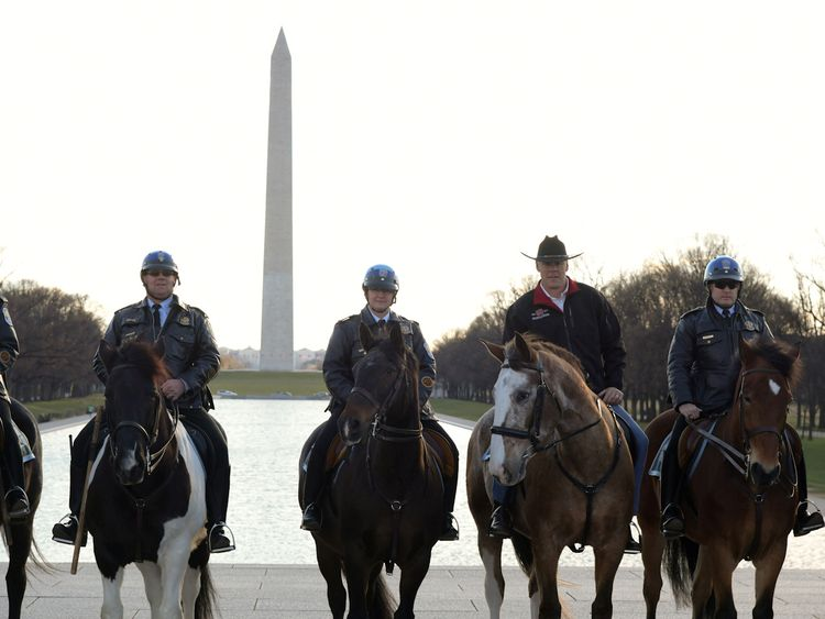 Ryan Zinke, second from right, rides on horseback while reporting for his first day of work