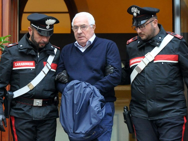 Settimino Mineo, jeweller and new head of the Sicilian mafia is escorted by carabinieri as he exits a police station after his arrest in Palermo