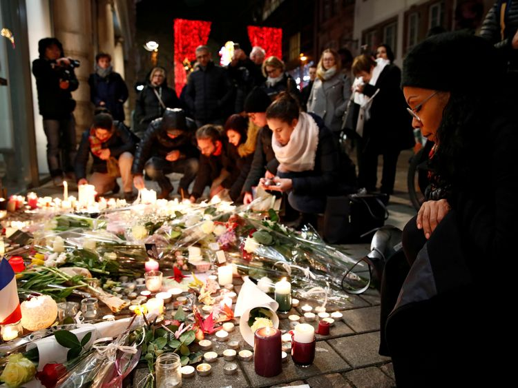 People cry as they light candles in tribute to the victims of the deadly shooting in Strasbourg, France, December 13, 2018
