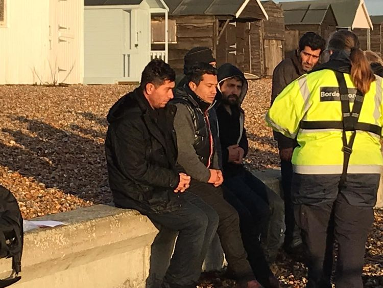 A Border Force official with suspected migrants on the beach at Kingsdown, Kent