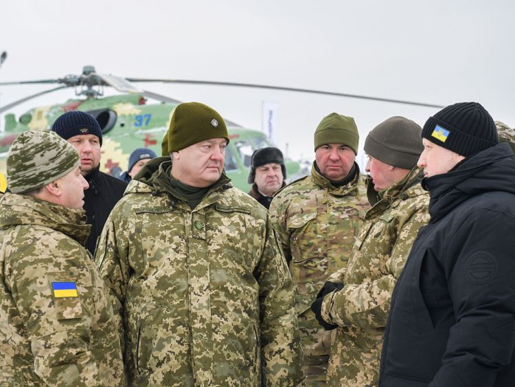 Mr Poroshenko (2nd L) and defence minister Stepan Poltorak (L) visiting an airbase over the weekend