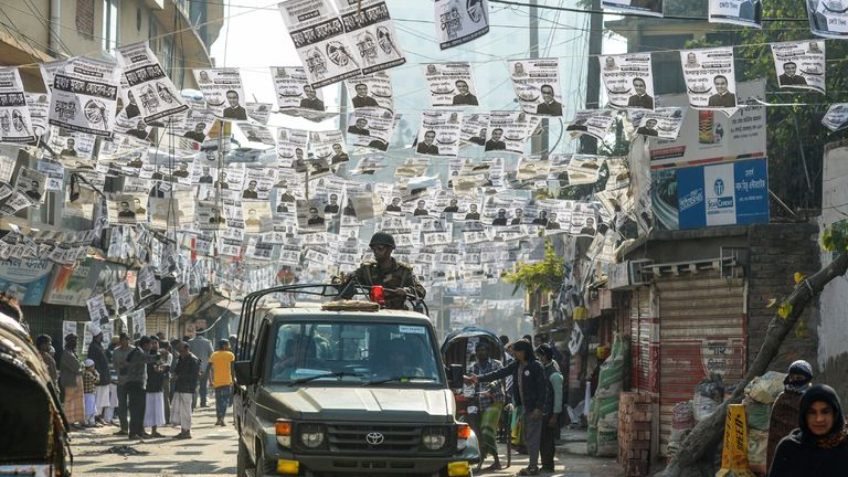Bangladesh army drives through a street adorned with election posters