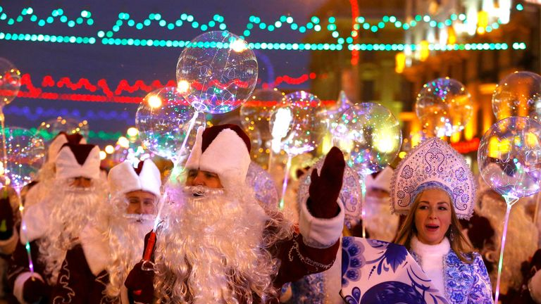 People dressed as Father Frost and Snow Maiden take part in a march on Christmas Eve in centre of Minsk, Belarus December 24, 2018