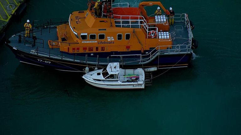 The RNLI tows a boat suspected to have been stolen by migrants