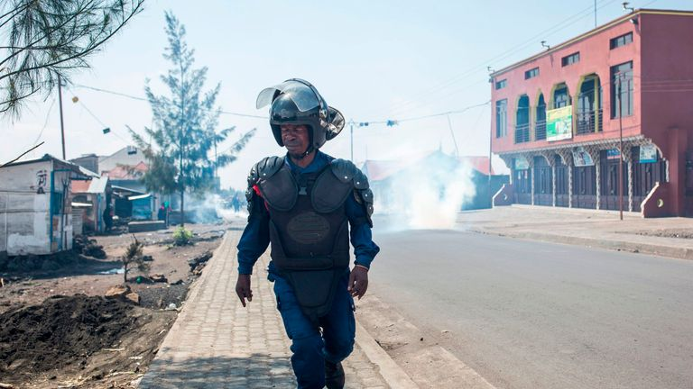 A police officer takes cover after a tear gas cannister was thrown
