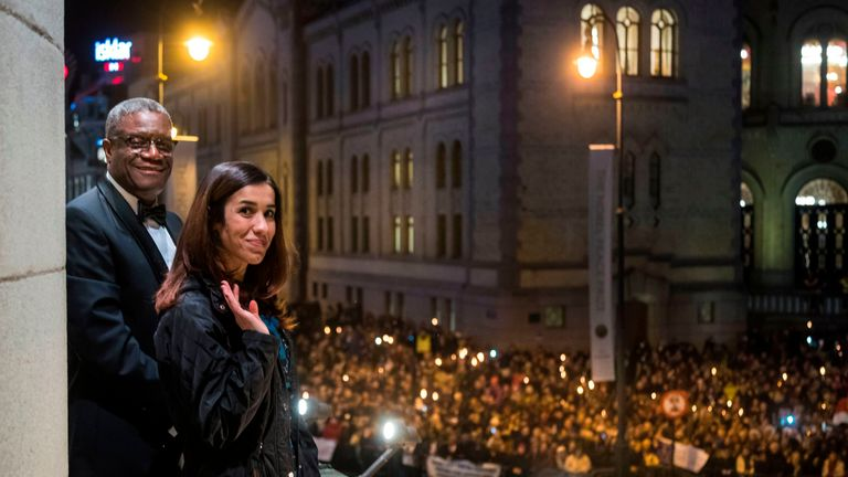 Nobel prize laureates Congolese gynaecologist Denis Mukwege (L) and Iraqi Yazidi-Kurdish human rights activist Nadia Murad wave people holding candles during a torchlight procession in Oslo downtown, Norway on December 10, 2018