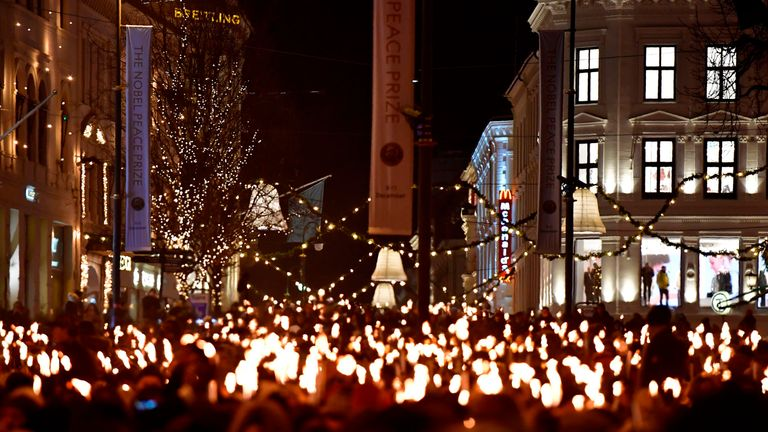 People walk in the streets of Oslo, Norway, holding candles during a torchlight procession to greet Nobel prize laureates Congolese gynaecologist Denis Mukwege and Iraqi Yazidi-Kurdish human rights activist Nadia Murad on December 10, 2018