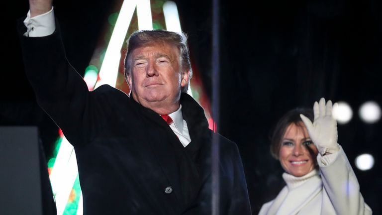 Donald and Melania Trump wave during the National Christmas Tree lighting ceremony