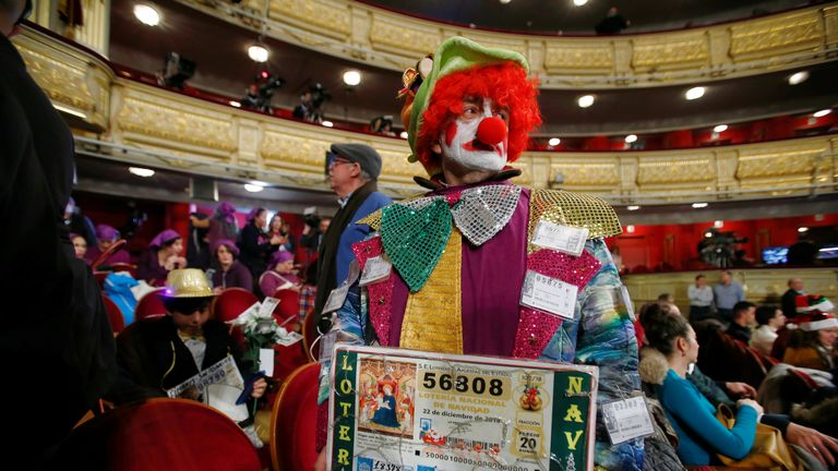 A man dresses a clown for the lottery day