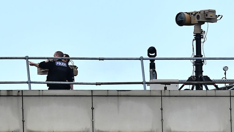 Police officers stand near equipment on the rooftop of a building at London Gatwick Airport, south of London, on December 21, 2018, as flights resumed following the closing of the airfield due to a drones flying. - British police were Friday considering shooting down the drone that has grounded flights and caused chaos at London's Gatwick Airport, with passengers set to face a third day of disruption. Police said it was a 'tactical option' after more than 50 sightings of the device near the airf