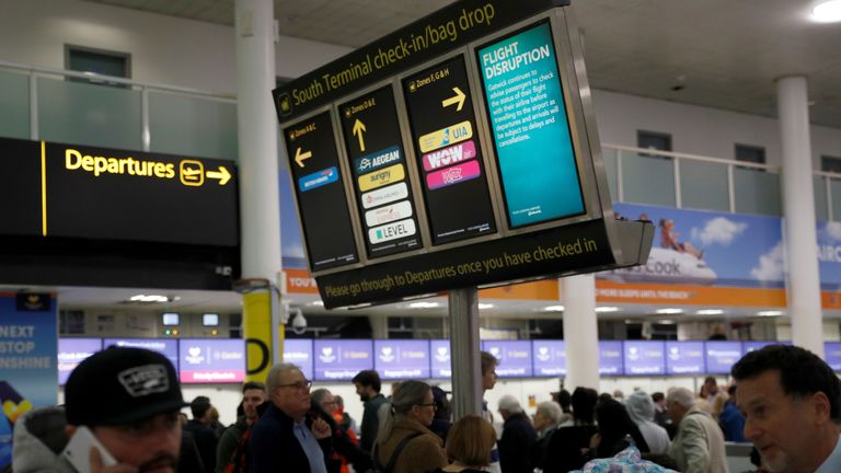 Passengers walk beneath screens displaying travel information in Gatwick Airport, in Crawley, Britain, December 22, 2018