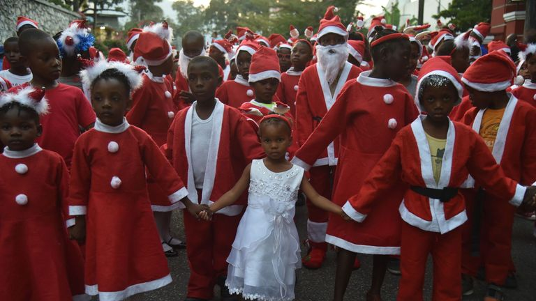 Haitian Children in Santa Claus costumes participate in a Christmas Parade (Parad Nwel in Haitian creole) on the streets of the commune of Petion Ville, in the Haitian capital Port-au-Prince, on December 23, 2018