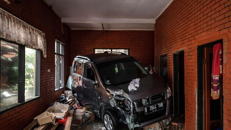A damaged car is seen inside a destroyed room in Carita