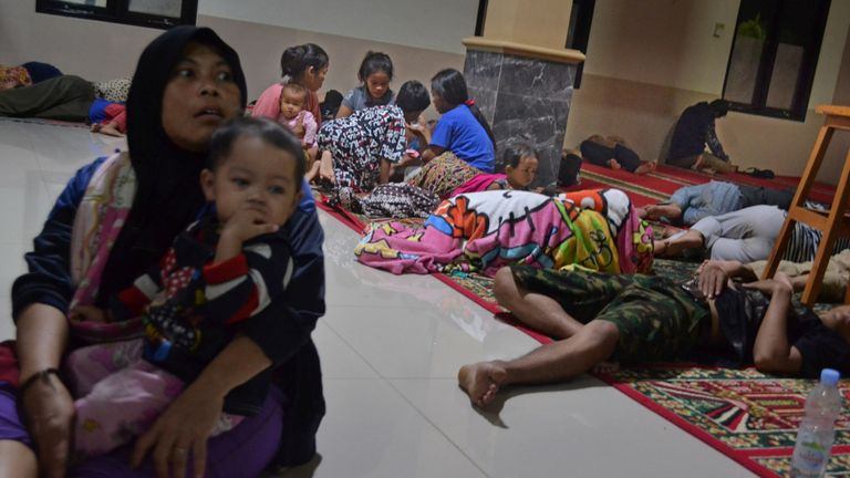 Indonesians wait in a mosque after being evacuated following high waves