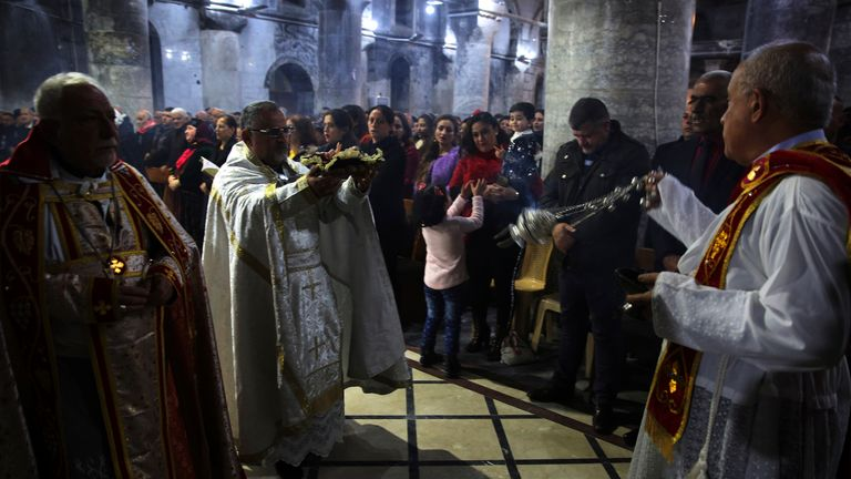 A priest leads mass on Christmas eve at the Grand Immaculate Church in the predominantly Christian Iraqi town of Qaraqosh, in the Niniveh province, some 30 kilometres from Mosul, on December 24, 2018