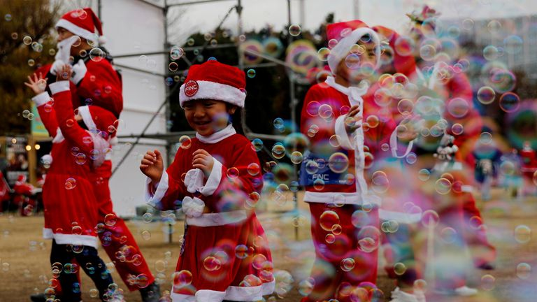 """Children dressed as Santa Claus chase bubbles at a charity event """"Tokyo Great Santa Run 2018"""" in Tokyo, Japan, December 23, 2018"""