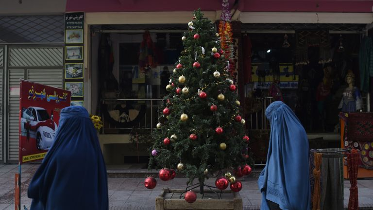 Afghan women wearing a burqa walk past a Christmas tree at the Shar-e Naw district in Kabul on December 24, 2018
