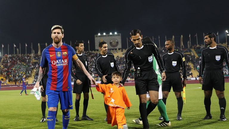 Messi clutches the young fan's hand before a friendly match in Qatar