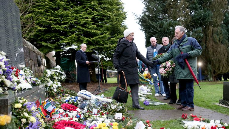 People pay their respects at the commemoration service in Lockerbie