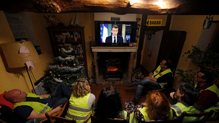 Protesters in yellow vests watch Mr Macron as he addressed the nation over weeks of protests