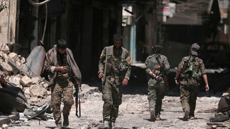 Syria Democratic Forces (SDF) fighters walk through Manbij after defeating IS in 2016