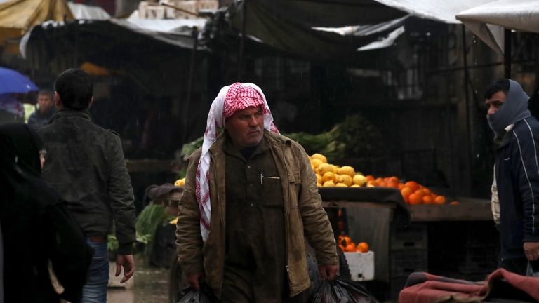 A Syrian man walks in a bazaar in the northern Syrian town of Manbij