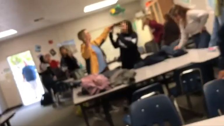 Margaret Gieszinger grabs a girl's hair as she hold scissors in her other hand. Pic: Logan_1002/Reddit