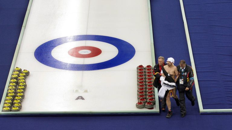 Mr Roberts is escorted away after he entering the course during a break in the curling at the Winter Olympics in Torino in 2006