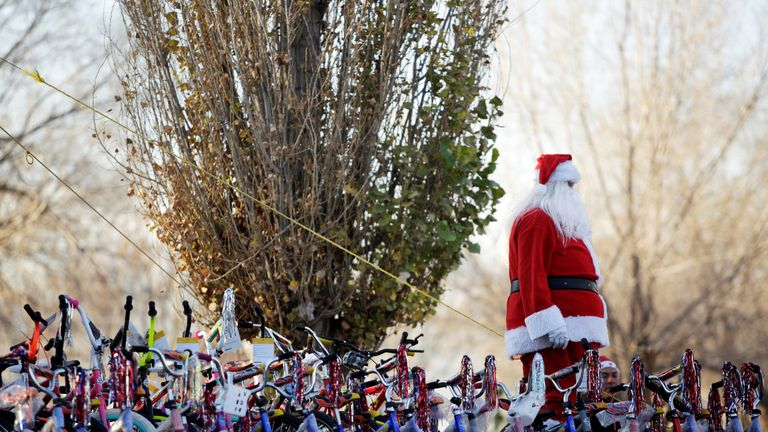 A firefighter dressed as Santa Claus stands by bicycles during the annual gift-giving event organised by the Fire Department, in which they hand out items donated throughout the year to children in need, in Ciudad Juarez, Mexico, December 24, 2018