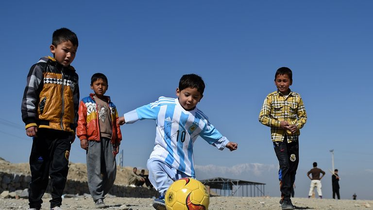 The youngster plays football in his signed Messi shirt