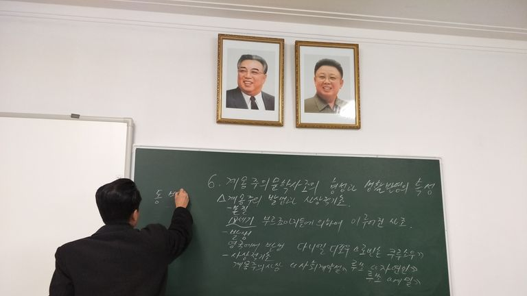 Alek's North Korean teacher writes on a blackboard with pictures of Kim Il Sung and Kim Jong Un above. Pic: Alek Sigley