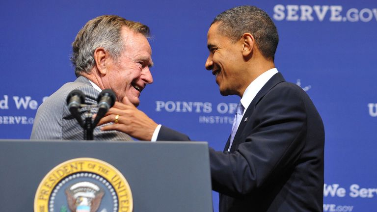 Former US president George H.W. Bush (L) greets President Barack Obama after introducing him on October 16, 2009