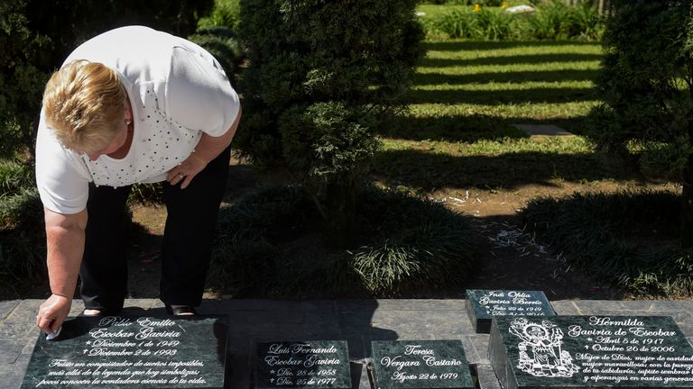 The sister of Pablo Escobar, Luz Maria Escobar, cleans a plaque on his tomb